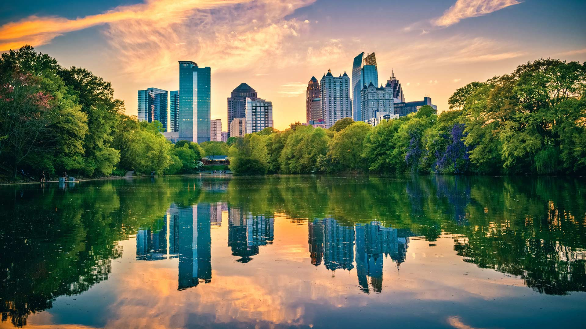 Atlanta Skyline with a pond surrounded by trees in the foreground.